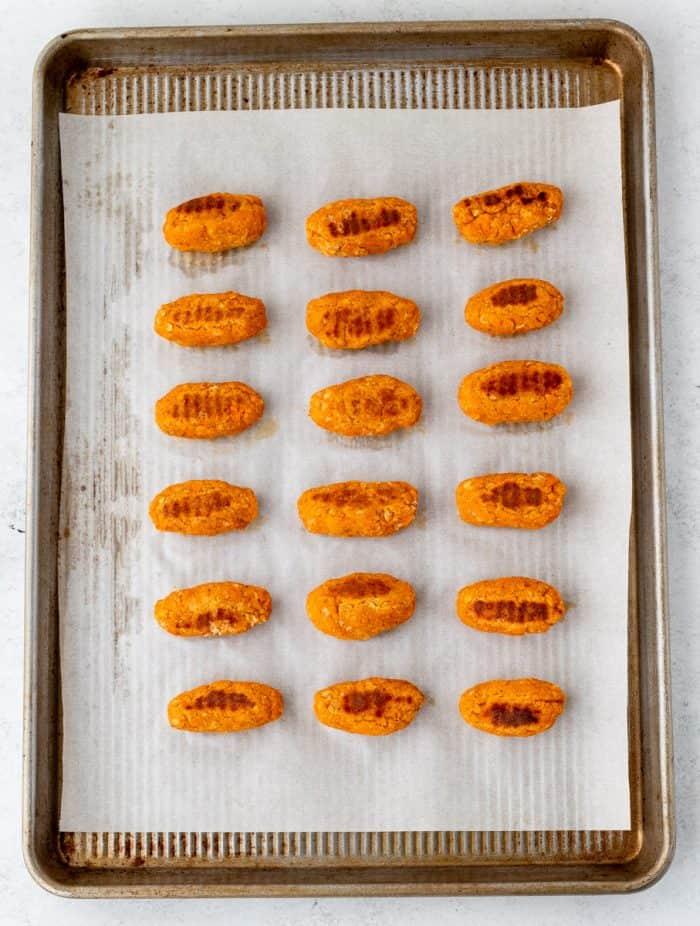 Baked sweet potato tots on a baking sheet.