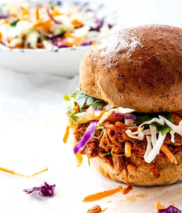 Pulled pork on a bun with coleslaw in a bowl