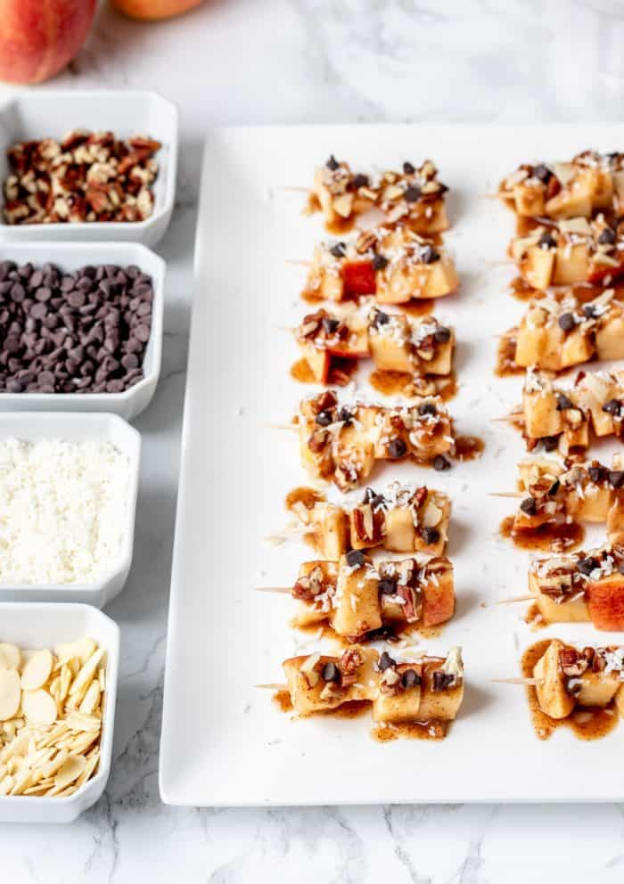 An apple skewer bar with toppings in bowls.