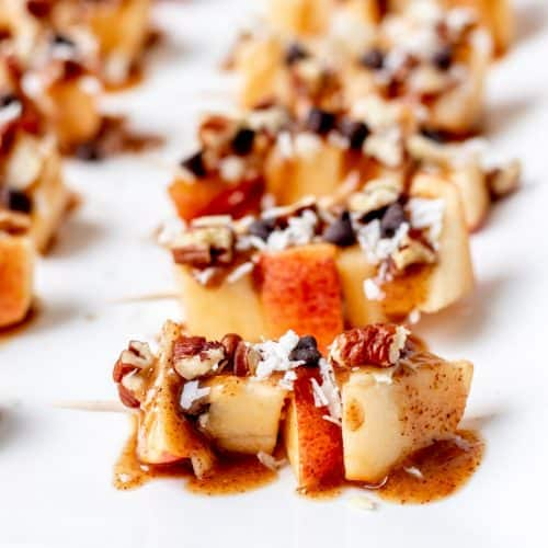 Apple skewers drizzled with caramel sauce and chopped nuts.
