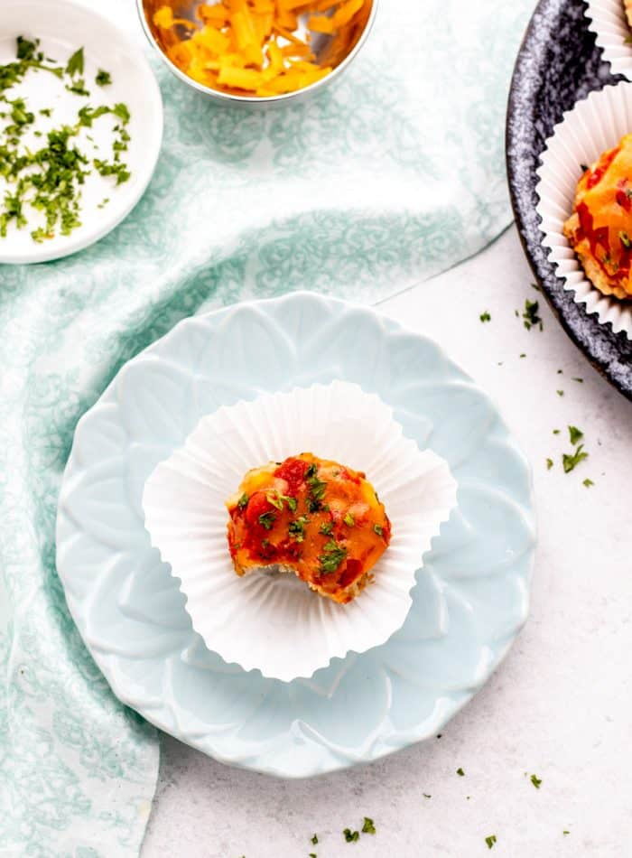 overhead shot of a meatloaf muffin on a turquoise plate in a white wrapper next to shredded cheese and parsley