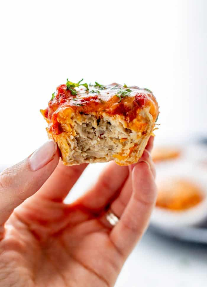 a hand holding up a chicken muffin with a bite taken out of it