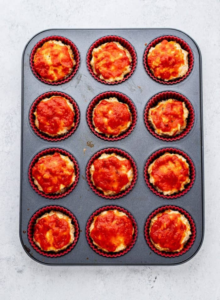 baked chicken muffins in a muffin tin topped with marinara sauce