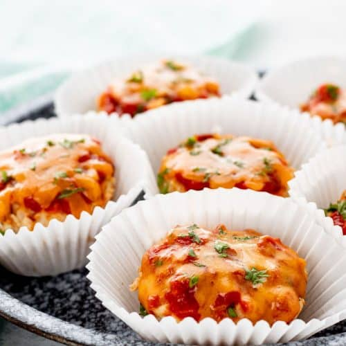 Baked chicken muffins in white muffin liners on a grey plate with melted cheese on top