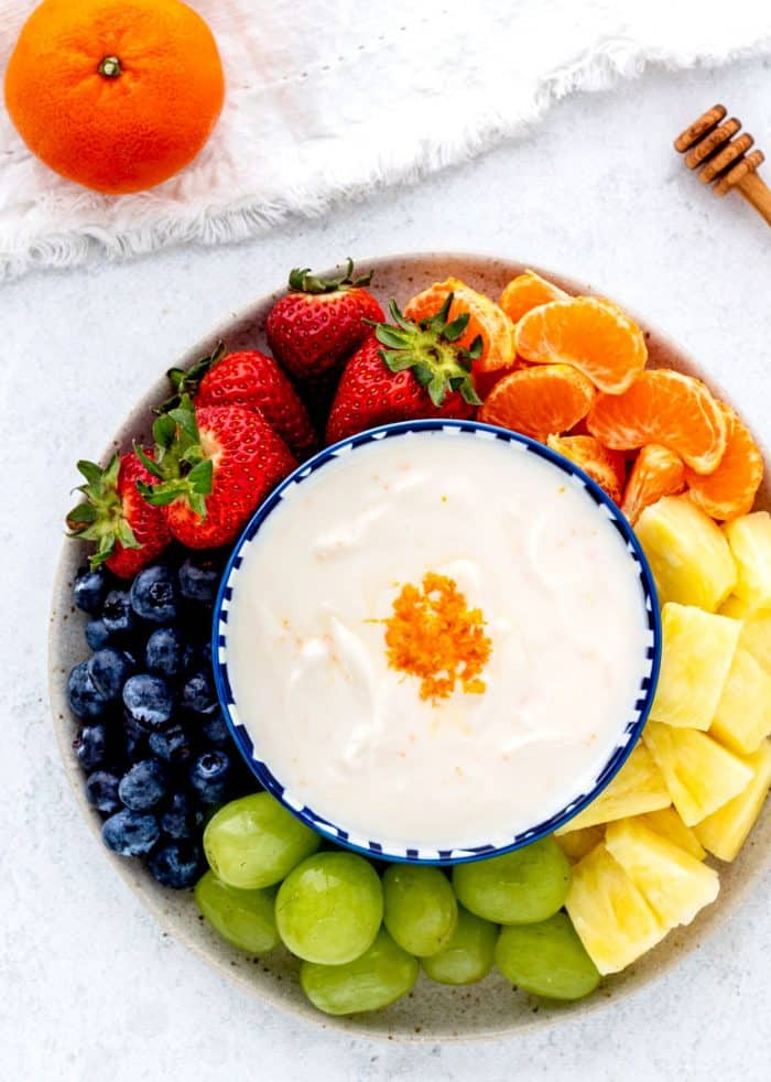 A yogurt dip served in the middle of a fruit platter.