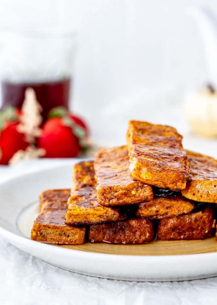 Close up of a stack of pumpkin French toast sticks on a white plate.