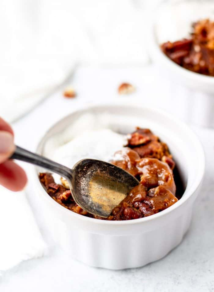 Digging a spoon in pumpkin cake with pudding and pecans in a ramekin