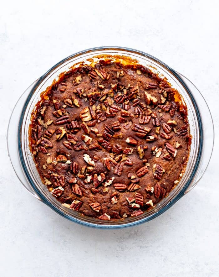 Baked pumpkin cake topped with pecans in glass baking dish